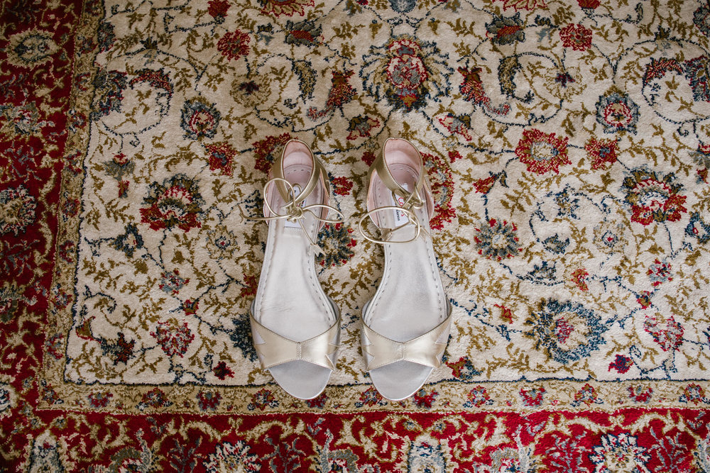dune wedding shoes on a patterned carpet in a cottage