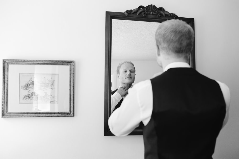 black and white photo of groom tying his bow tie on the morning of his outdoor wedding