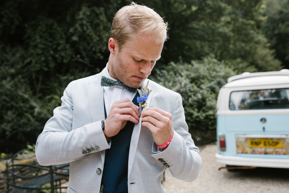 groom wearing reiss suit putting on his wild flower buttonhole