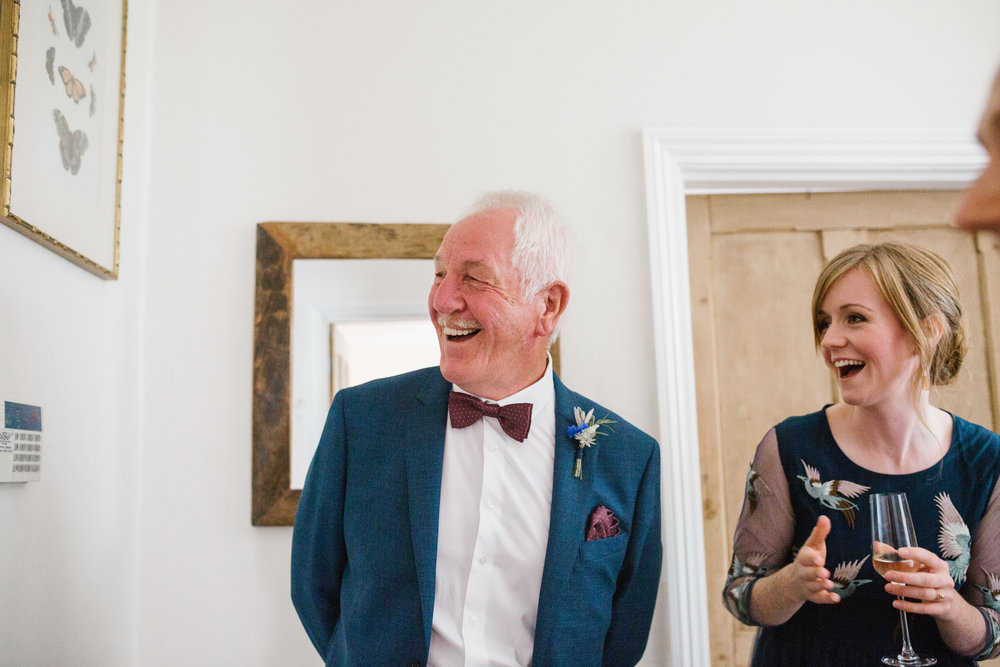 natural photo of father of the bride smiling as he sees his daughter for the first time