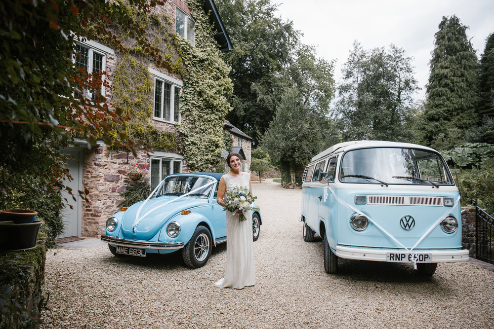 blue vw campervan and vw beetle as wedding cars for the outdoor wedding ceremony