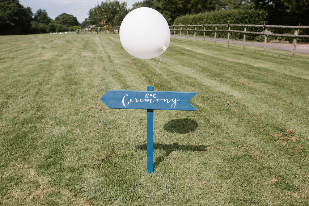 homemade signpost to the outdoor festival wedding