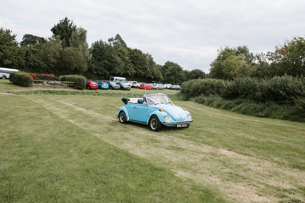 light blue vw beetle arriving with bride and father of the bride at outdoor wedding ceremony