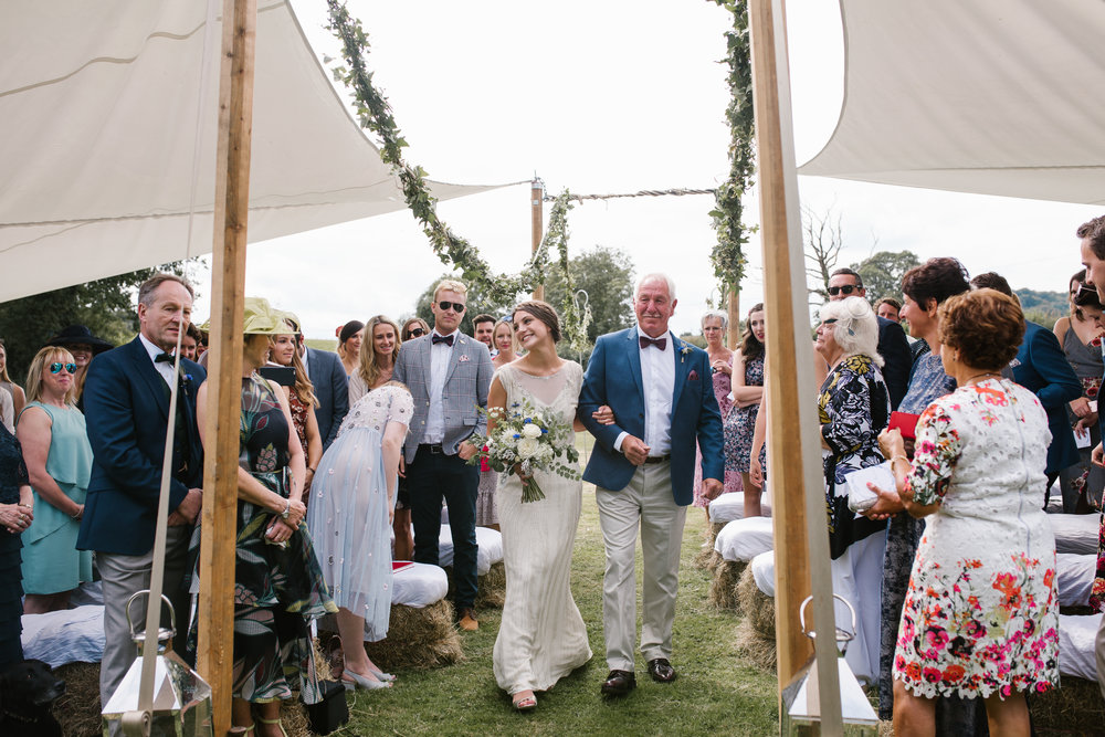 natural photo of bride and father of the bride walking down the outdoor wedding aisle at boho wedding