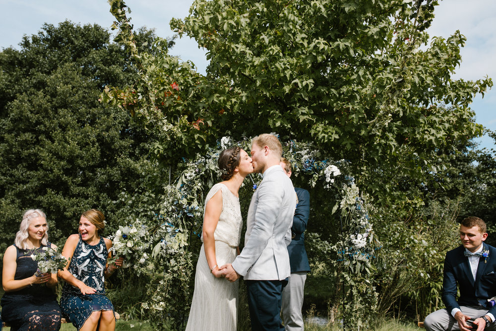bride and groom kissing at their outdoor wedding ceremony