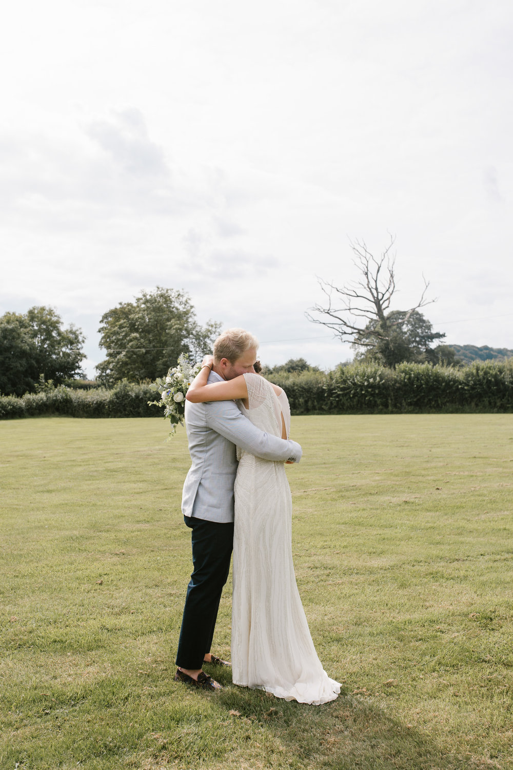 natural photo of bride and groom hugging after their outdoor wedding ceremony