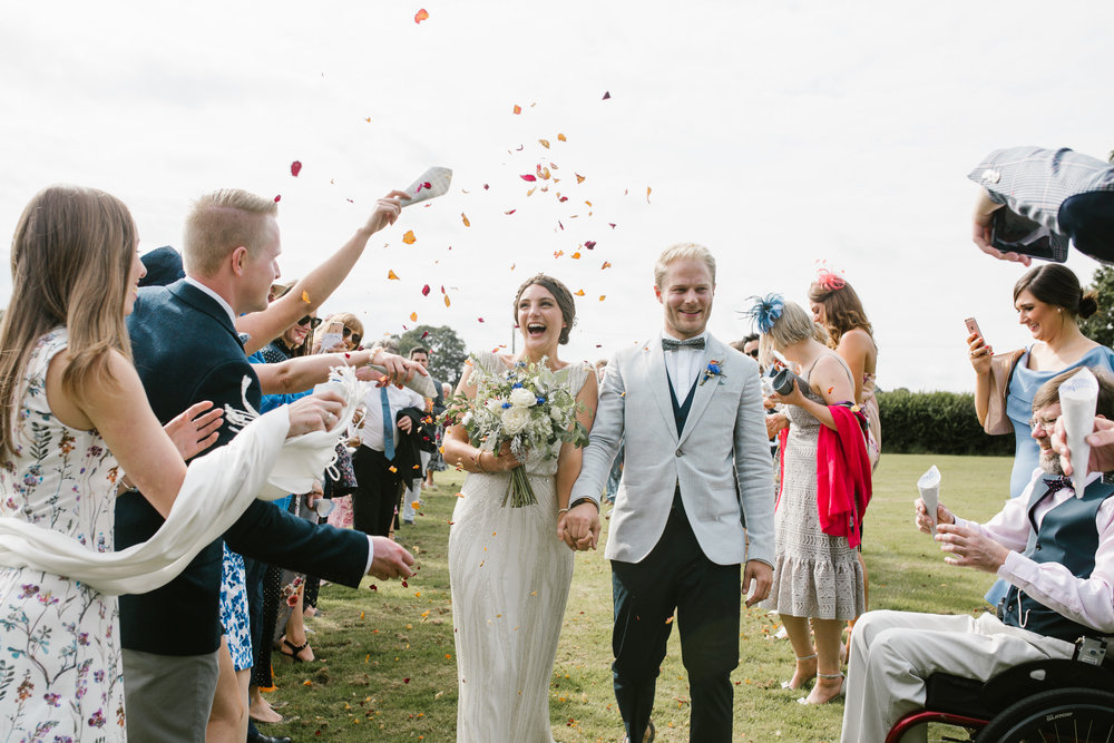 boho brode and groom being showered in confetti after their outdoor wedding