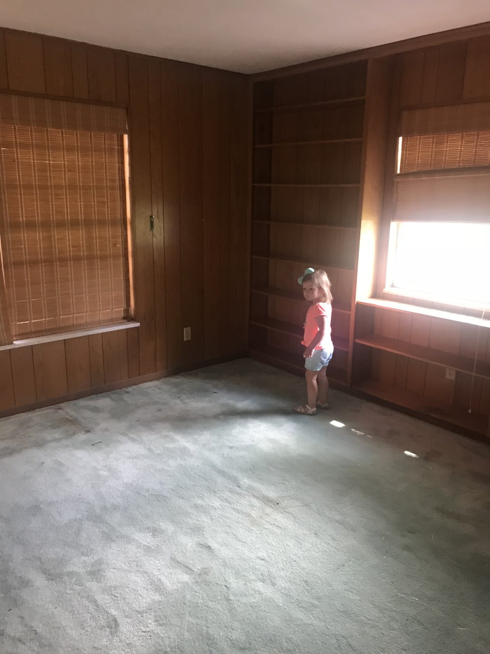This is the current study that we are moving the master bedroom to. We are adding an additional window in this room to frame the bed in between along the wall Sutton is currently standing next to. Should we keep the wood paneling? Ok ok I'll stop with the rhetorical questions ;)