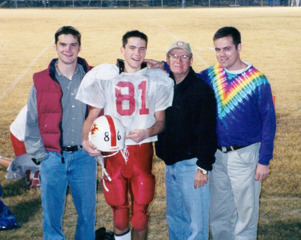 Here I am with my dad and two brothers. This was taken during my senior season of football. My dad got really sick when I was in high school. I'm pointing at the number 86 which was his number in high school.