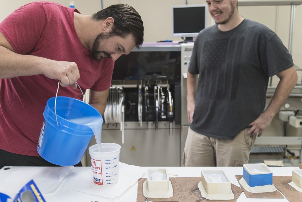 David mixes resin to make the other mold half to be used for rotocasting after it has cured.