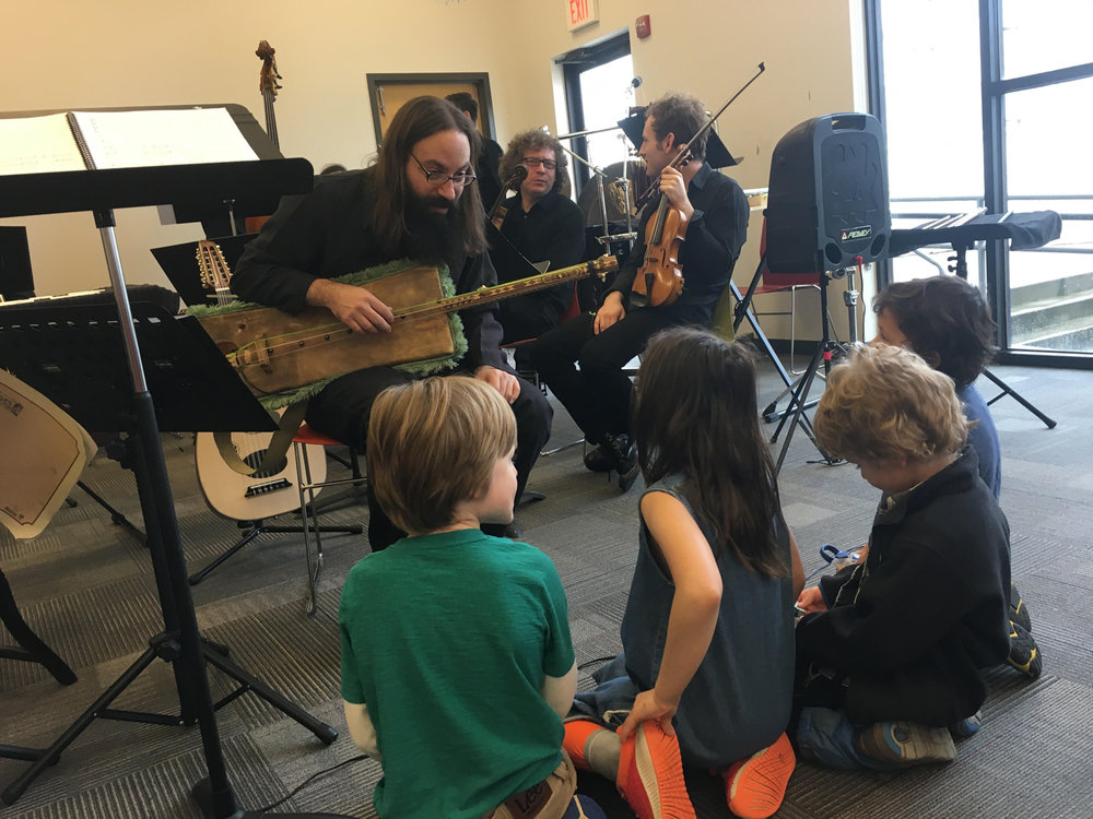 COMMUNITY OUTREACH.  Shanir Ezra Blumenkranz plays gimbri, a traditional Moroccan instrument, to the children at  Hello Gold Mountain 's Casa Azafran community performance with chatterbird.