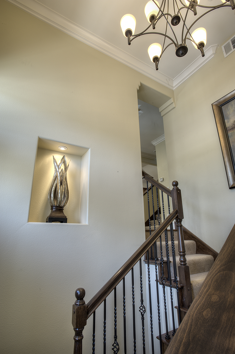 Stairway with chandelier above and a figurine