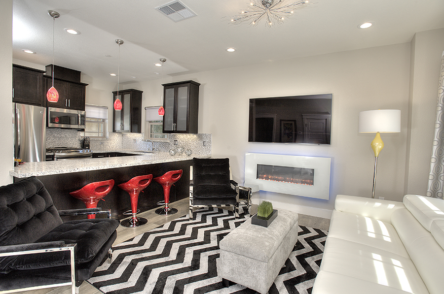 Modern living room with three red chairs and a black and white floor mattress and television