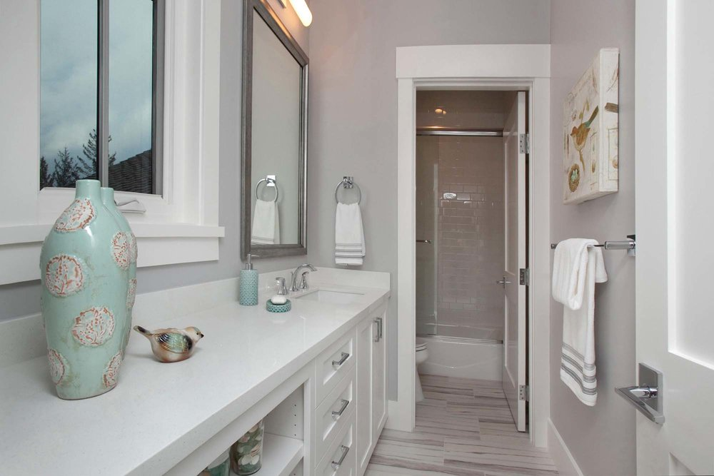 Bathroom with white furnishing, vase and mirror