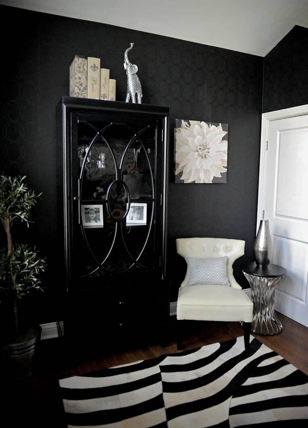 Home office with black cabinet and a zebra style floor mattress