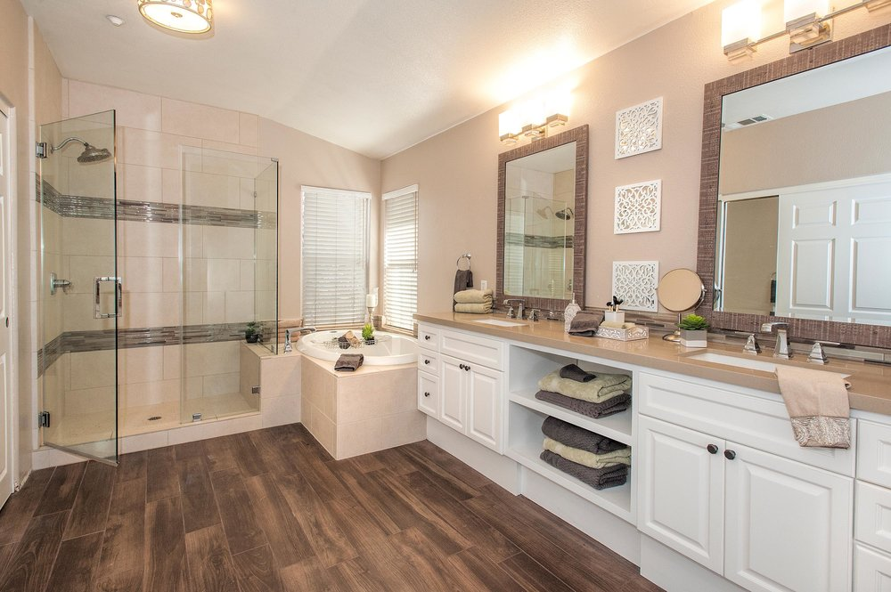 Vintage look bathroom with elegant hardwood flooring and white cabinet
