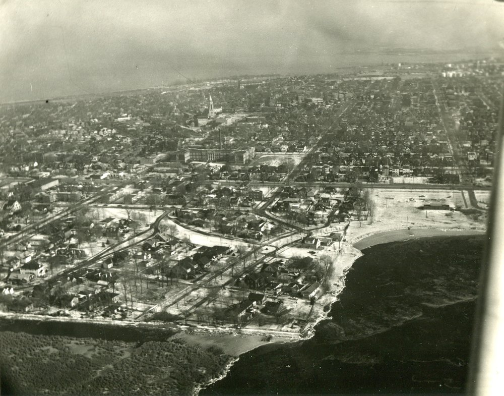 This aerial shot shows Wolf Lake in the bottom right part of the photo. and the Water Gardens to its left. The white swath just below the center of the photo is where Moylan's Lagoon was located, and the smaller white patch at the left end of it is Forsythe Square. This photo was probably taken in the early 1960s.