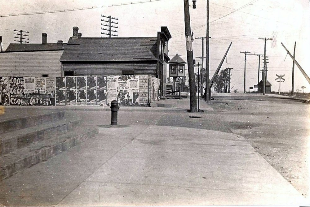 The intersection of 119th Street and Front Street, the eastern end of 119th. This is how it looked in the 1910s or 1920s. Front Street is on the right, with the crossing gates and railroad tracks leading to the lakefront, while 119th is seen in the center of this photo going to the left, or west.