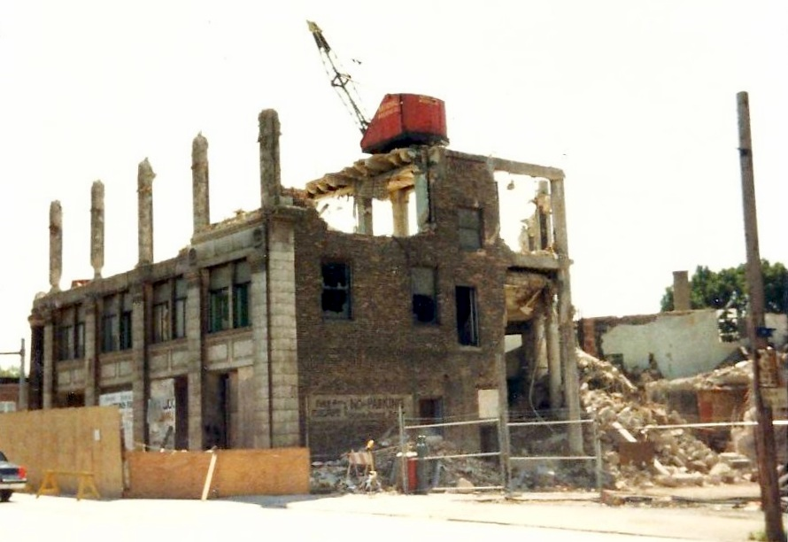 A demolition crane sits on top of the remaining floors of the Central State Bank Building as the building comes down in 1986. This is a view, from 119th Street looking toward Indianapolis Boulevard, of the backside of the building.