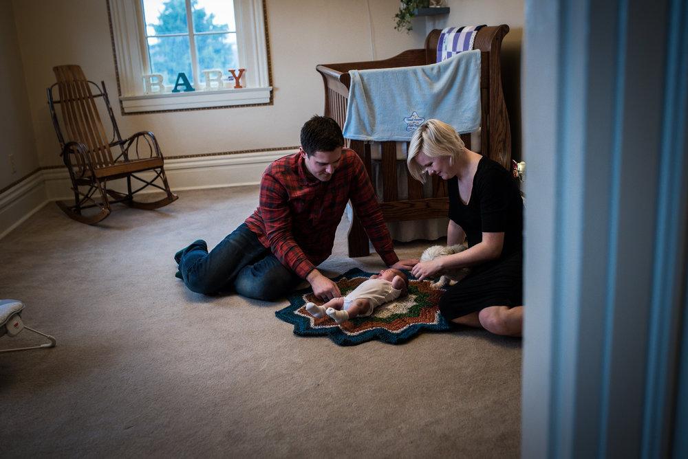 Postpartum photo session with newborn in nursery