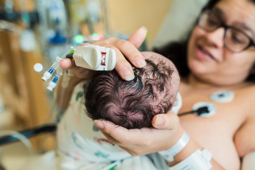 mom touching newborn's head birth photography pittsburgh