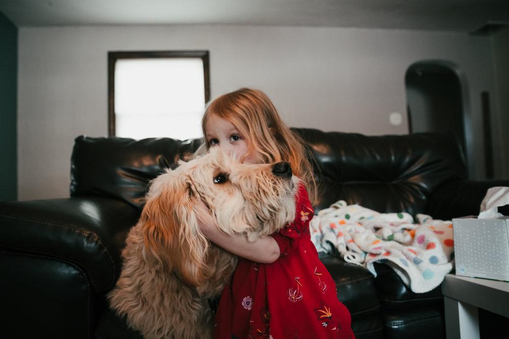 child giving dog kisses