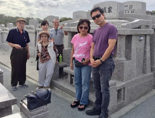 Janice Suetomi and her children pay respects to her ancestor at the dhaka in Okinawa.