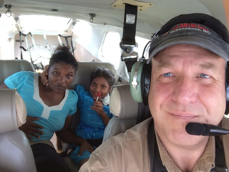 Precious cargo – MAG pilot Sean Donnelly flies a 4-year-old surgical patient and her mother back to their village after the IHS surgical team successfully removed a tumor from the girl's neck. The lollipop helped too!