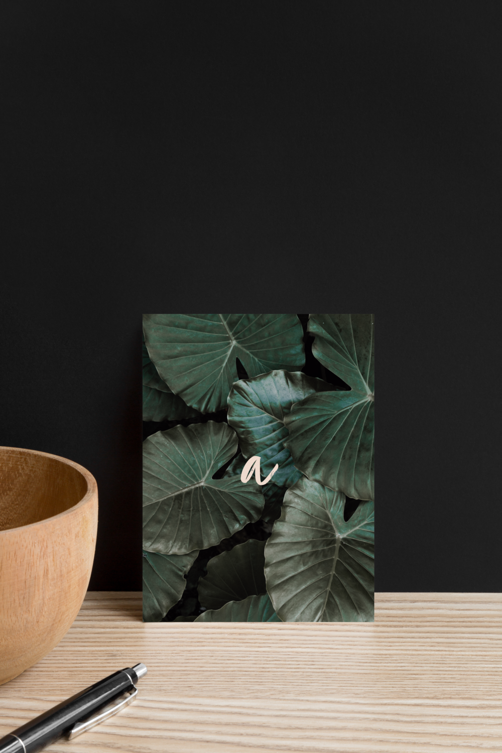 Postcard designed for Alexa mazzarello with her logo and leaf photo shown on a wooden shelf next to a black pen and a wooden bowl