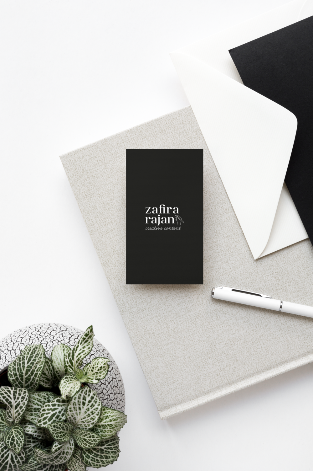 Zafira Rajan's business cards shown on top of a grey notebook, next to a black envelope and a light green plant