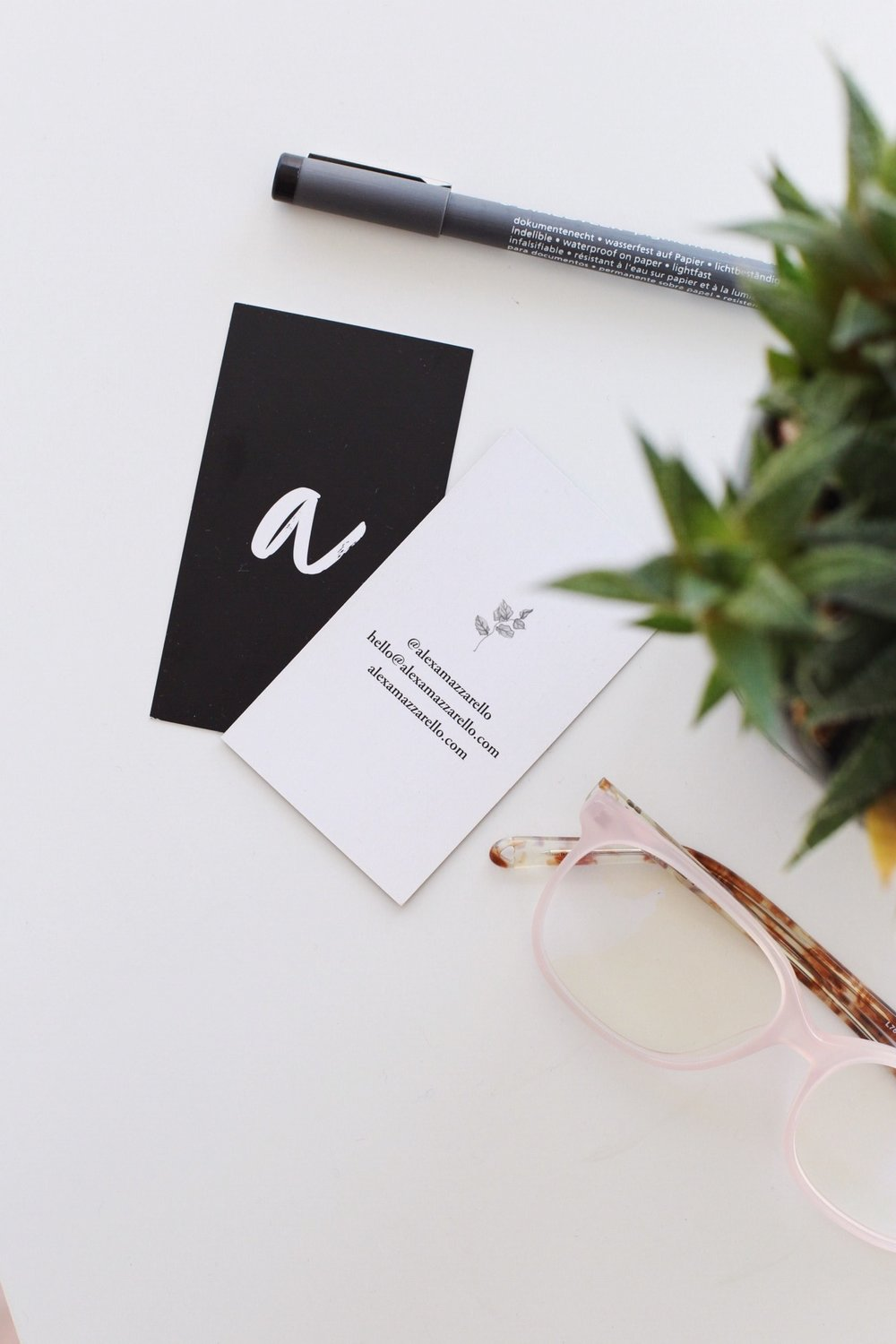 Alexa Mazzarello's Business Cards shown on a plain background with a green leaf, pink glasses and a pen.