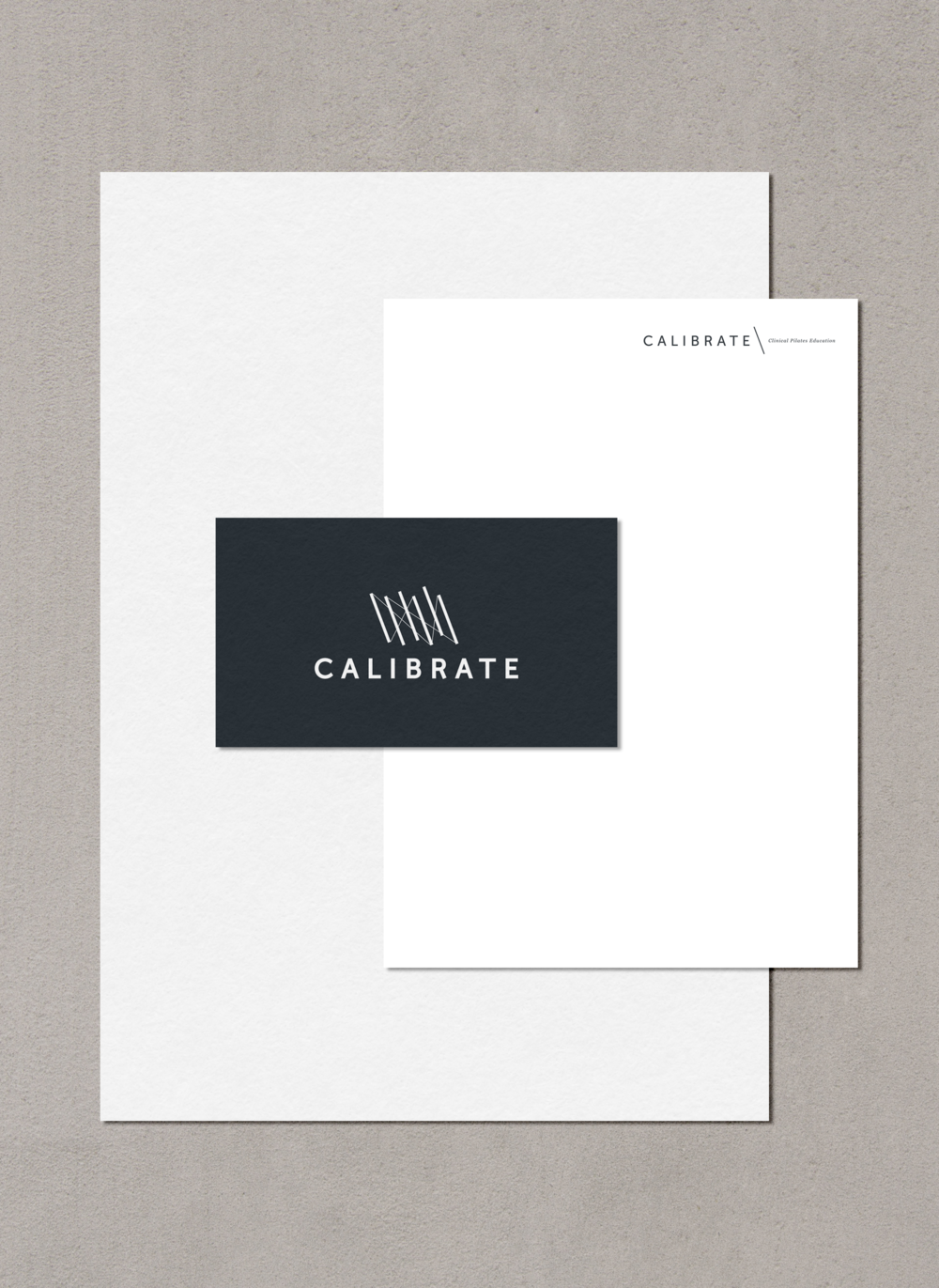 Calibrate Pilates logos on a business card, a letterhead, and a concrete background