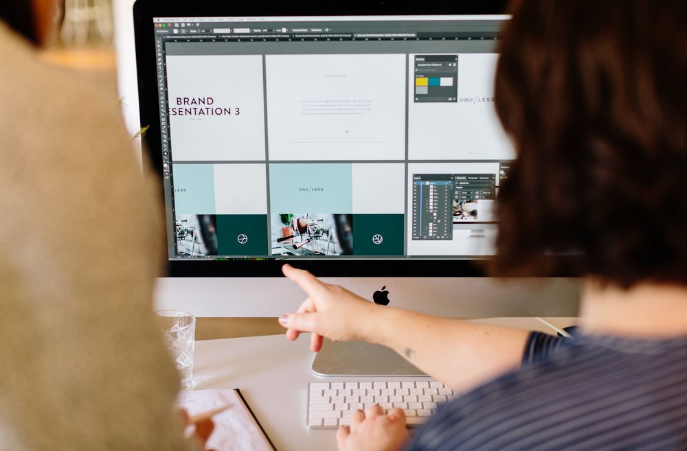 Lucy's hand pointing at an iMac with a Brand Presentation on display.