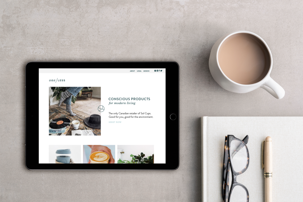 one less website mockup on an ipad next to a coffee cup and notepad