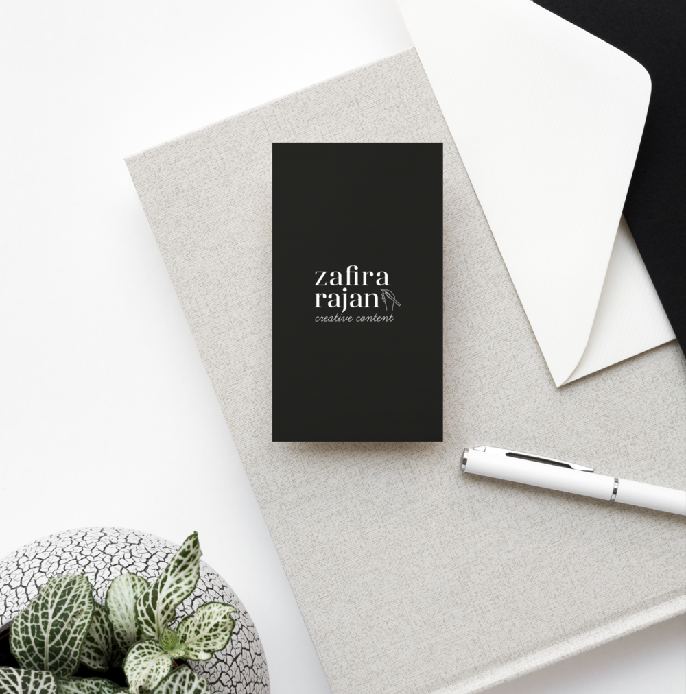 Zafira Rajan's logo on black business cards next to a small green plant and a white envelope