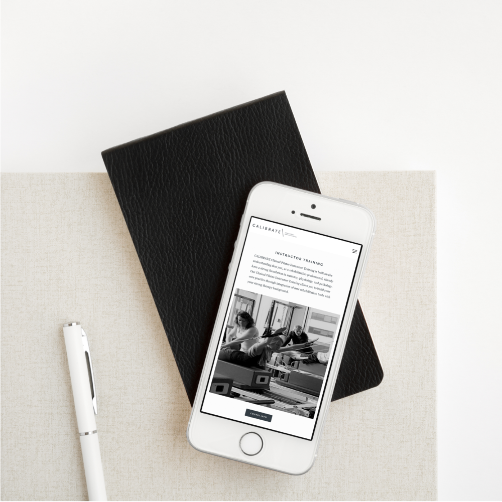 Calibrate Clinical Pilates Instructor Training website show on a mobile phone sitting on top of a black notepad next to a white pen.