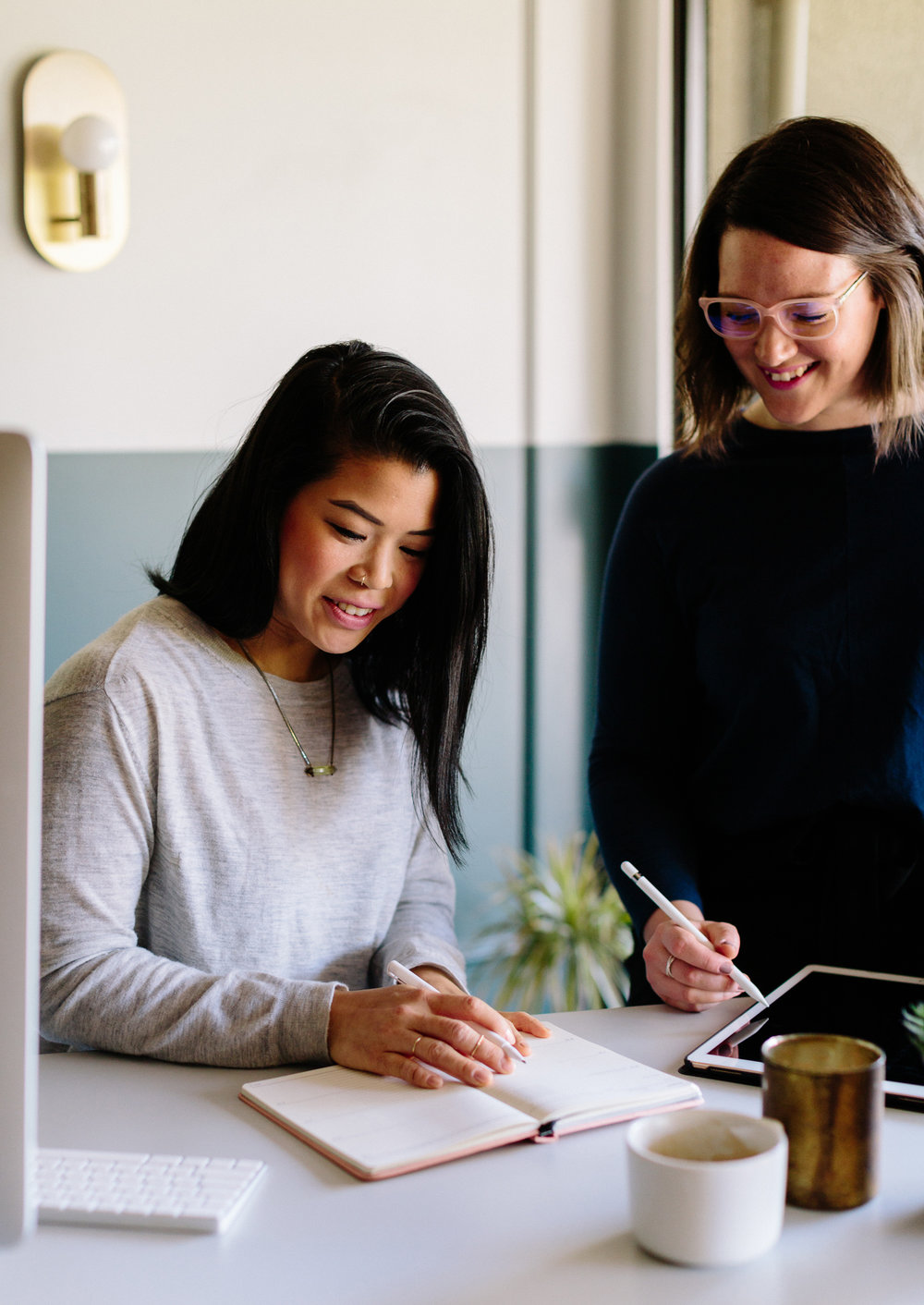 Daphne and Lucy from Salt Design Co. sat at a desk with a notebook and ipad, both smiling