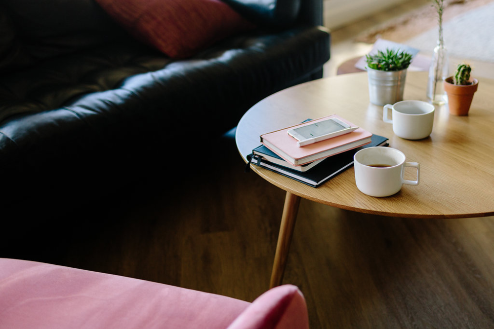 Notebooks and a phone on a coffee table in a warm living room style office