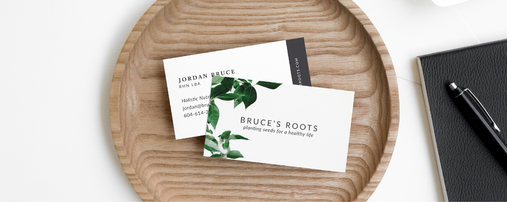 Bruce's Roots business cards designed by Salt Design Co. on a wooden bowl
