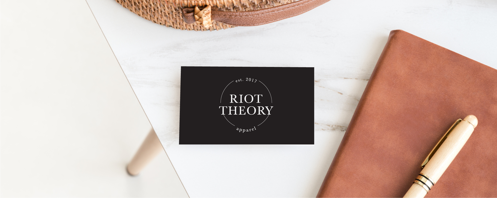 Riot Theory Black business card on a marble background