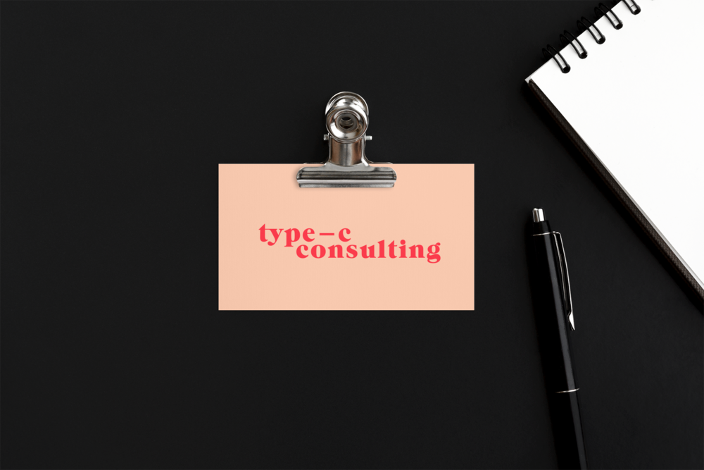 Type C Conuslting logo in red on a pink business card and a black paper background with a black pen