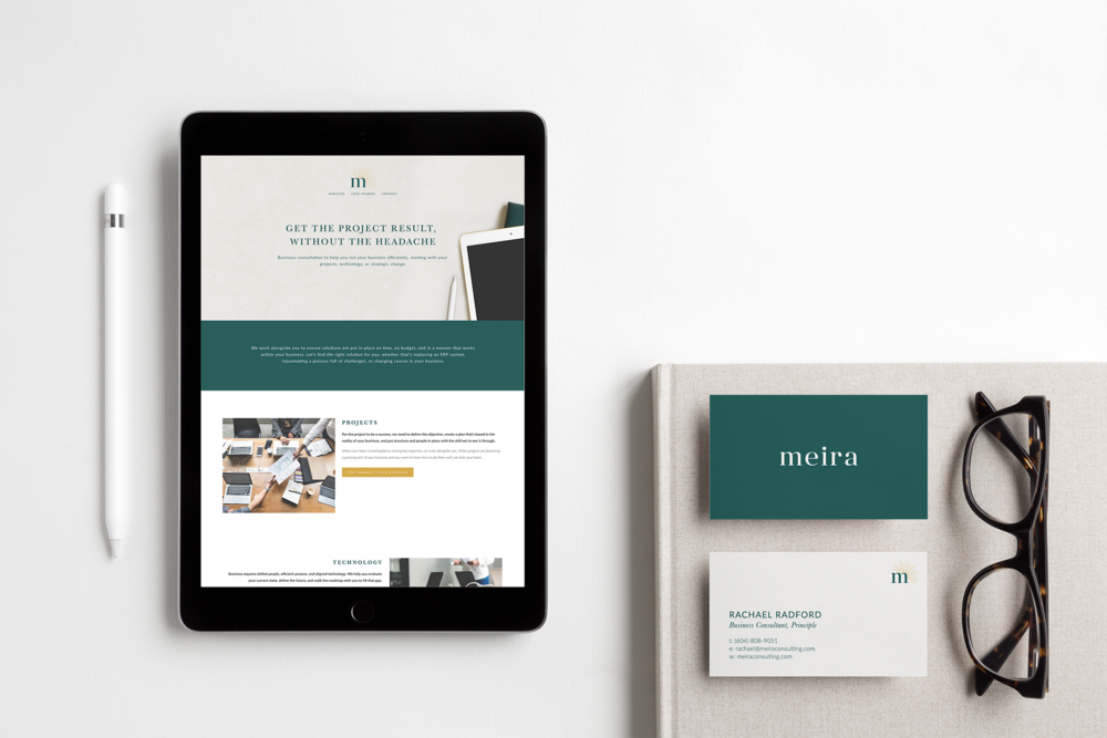 Meira Consulting website and business cards in forest green on a grey notebook with glasses next to them