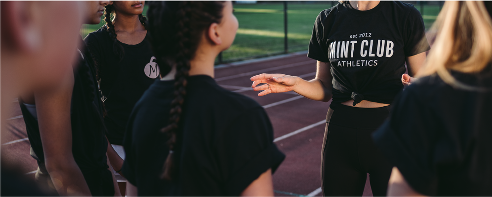 Mint Club Athletics logo on a black t-shirt worn by a woman surrounded by a group of teen girls. Photo by Kezia Nathe
