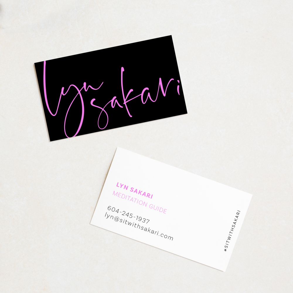 Lyn Sakari's black and pink business cards are shown on a soft grey background