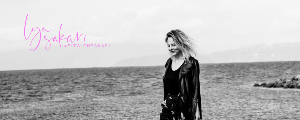 Header image with a photo of Lyn Sakari walking on a beach in black and white, and the logo for 'Lyn Sakari, #sitwithsakari' on top of the photo in bright pink