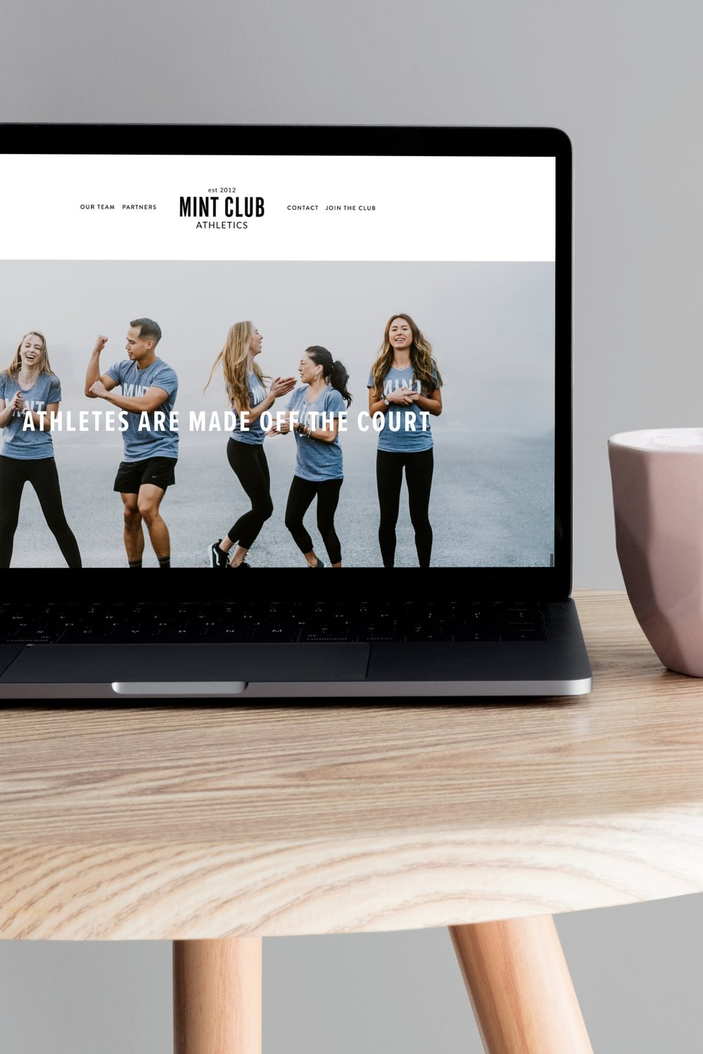 Mint+Club+Athletics+website+on+a+Macbook+Pro+next+to+a+pink+cup