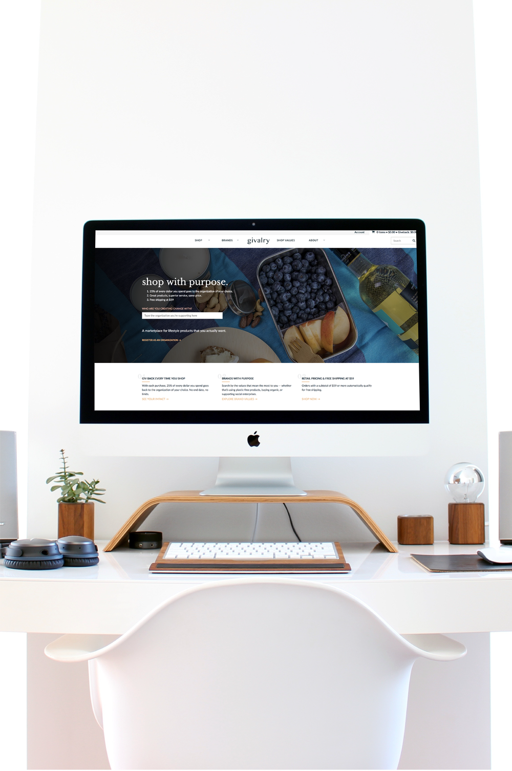 """Givalry website main homepage header with text reading"""" Shop with purpose"""" on a background of tin lunch containers displayed on an iMac on a wooden stand, on a white desk with a wooden keyboard and white chair."""