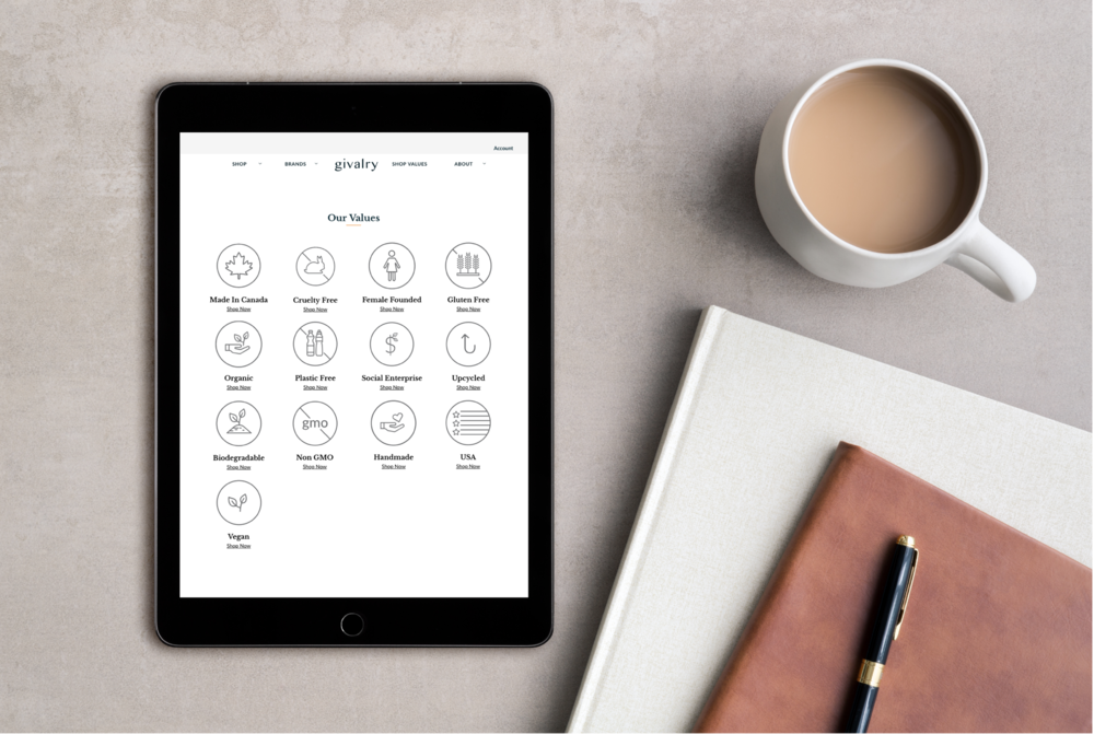 Givalry website of value icons on an iPad sitting beside a cup of coffee and a pen atop a notepad and book.