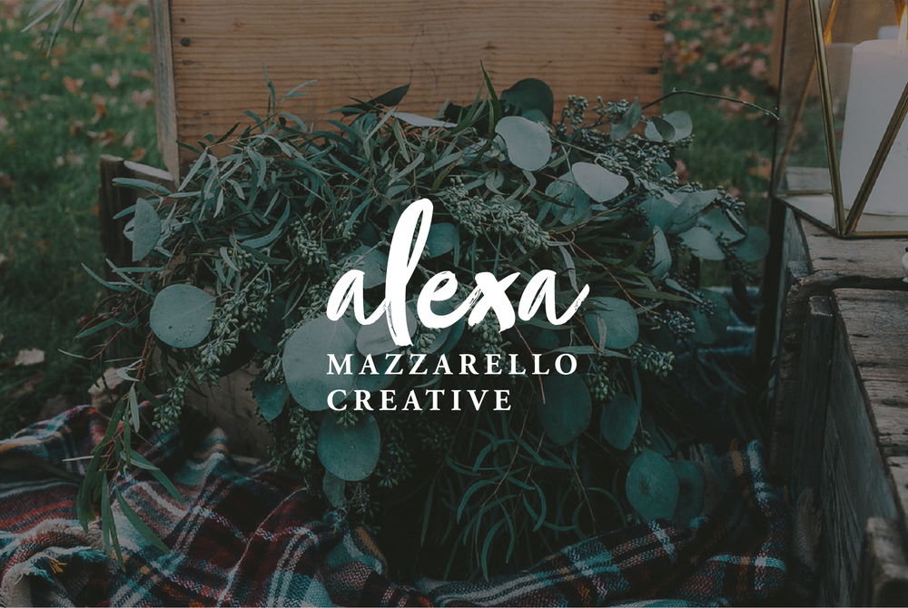 Alexa Mazzarello Creative logo overlaid on top of a moody image of dark green plants inside a wooden crate on a plaid blanket.