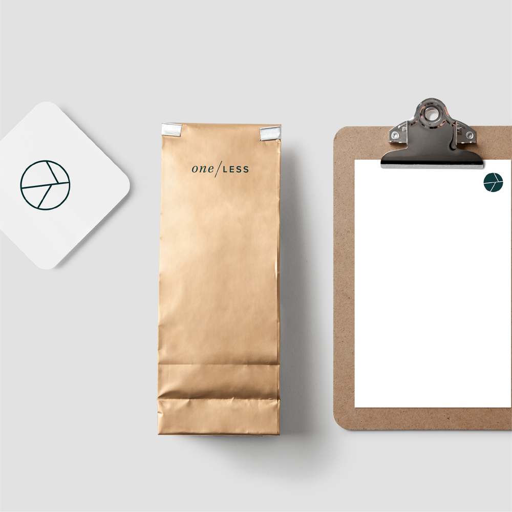 One Less branding an icon on a coffee bag, coaster and clipboard